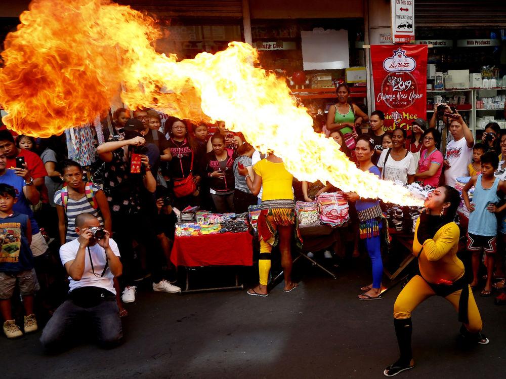 Artista de rua executa manobra com fogo durante as celebrações do Ano Novo Lunar em Manila, Filipinas, 5 de fevereiro de 2019