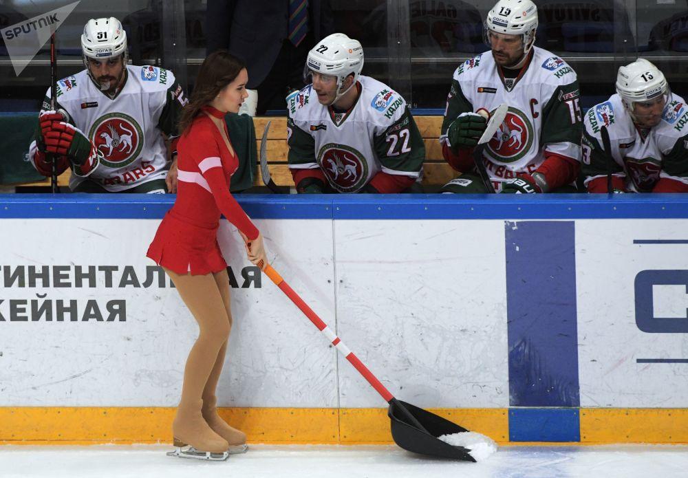 Jovem do grupo de apoio arruma a pista de gelo durante jogo da Liga Continental de Hóquei