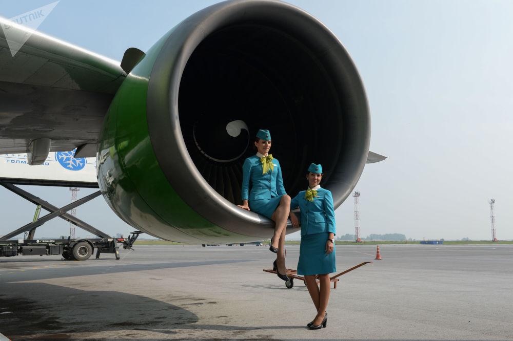 Aeromoças da companhia aérea S7 tiram foto na pista do aeroporto de Novossibirsk