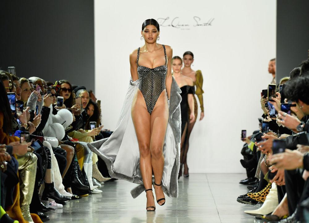 Jovem arrasta casaco pela passarela, mostrando todas suas curvas para o público do New York Fashion Week.