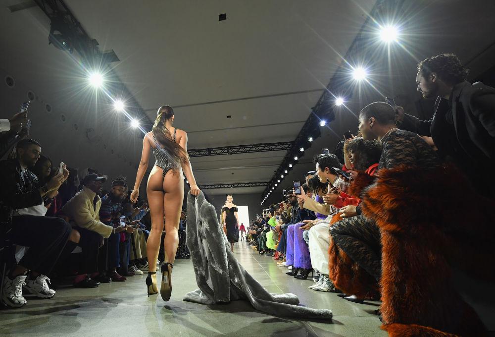 Arrastando caso pela passarela, modelo é filmada por todos os espectadores usando apenas um maiô