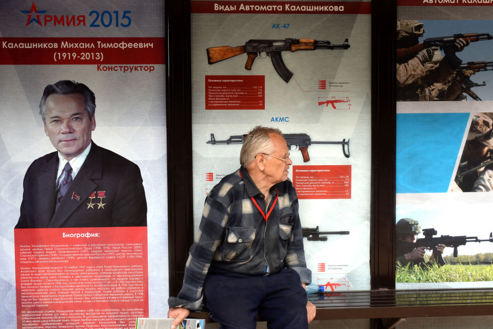 As imagens de fuzis do Consórcio Kalashnikov atras de um homem.