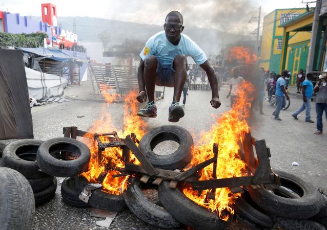 Manifestante salta sobre uma barricada em chamas durante protesto contra o governo nas ruas de Porto Príncipe, no Haiti, em 10 de fevereiro de 2019