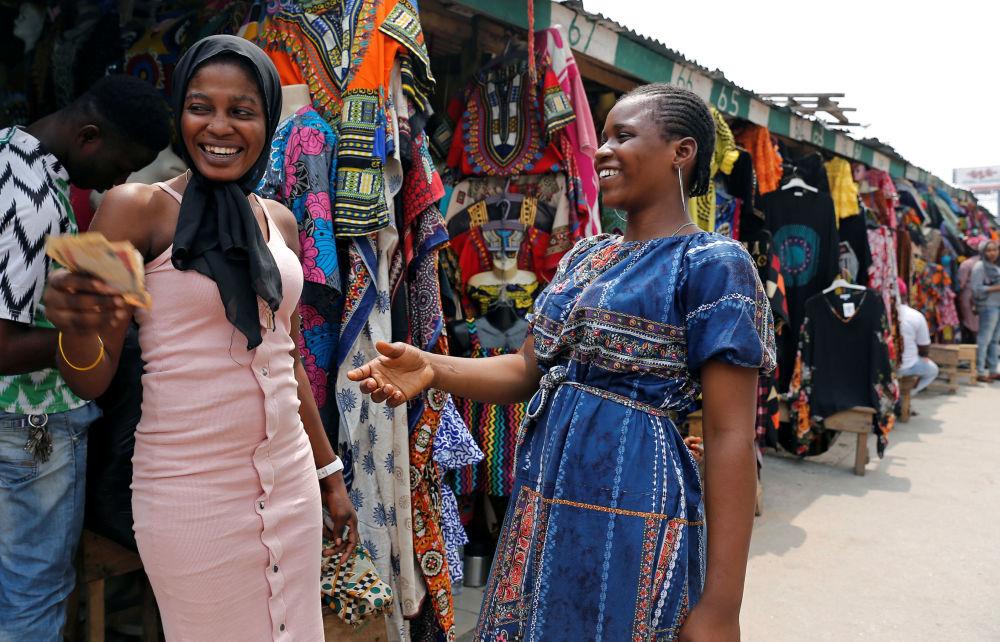 Vendedores de roupas trocam dinheiro em Marina, na capital comercial da Nigéria, em 11 de fevereiro de 2019