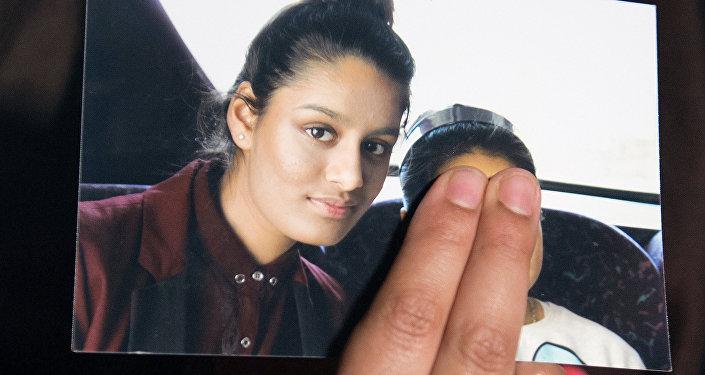 Irmã da adolescente britânica Shamima Begum, segura uma foto de sua irmã apelando para ela voltar para casa, em Scotland Yard, Londres