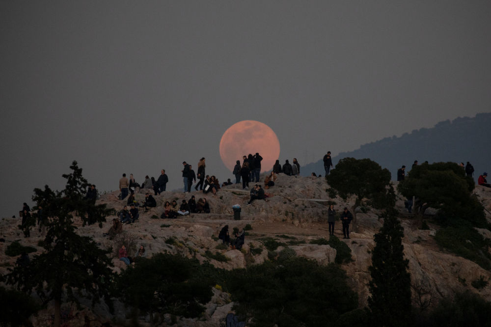 Superlua vai subindo aos olhos de visitantes no monte Areópago, Grécia