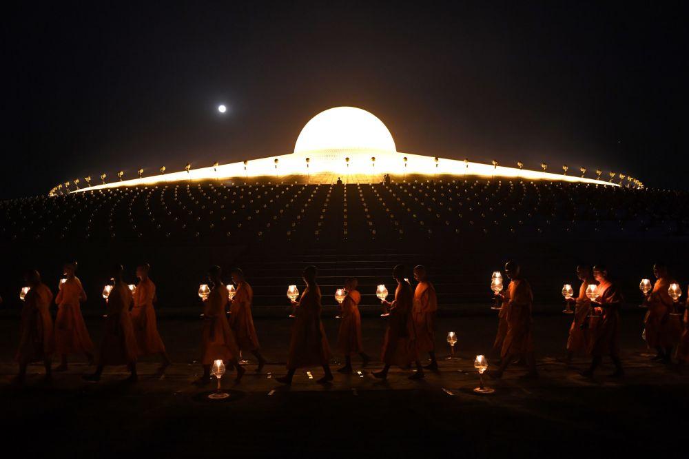 Monges budistas acendem velas para a Lua cheia durante orações no Dia de Makha Bucha no templo de Wat Phra Dhammakaya, perto de Bangkok