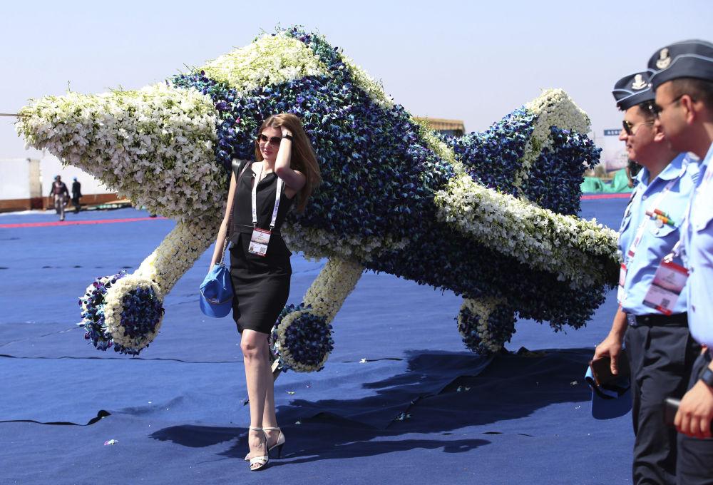 Exibidora estrangeira na exposição Aero India 2019 em Bangalore posa ao lado de um avião de flores