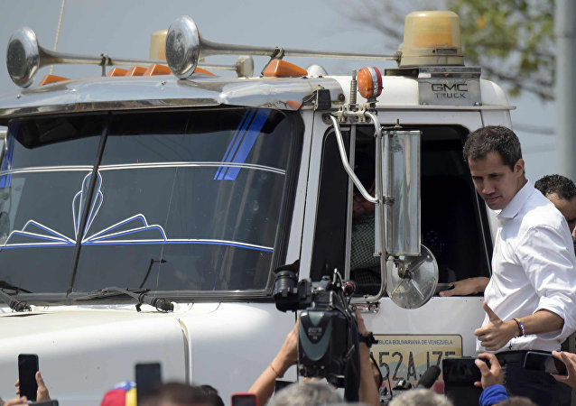 O líder da oposição venezuelana, Juan Guaido, dá sinal de ok da lateral de um caminhão que transportava ajuda humanitária.