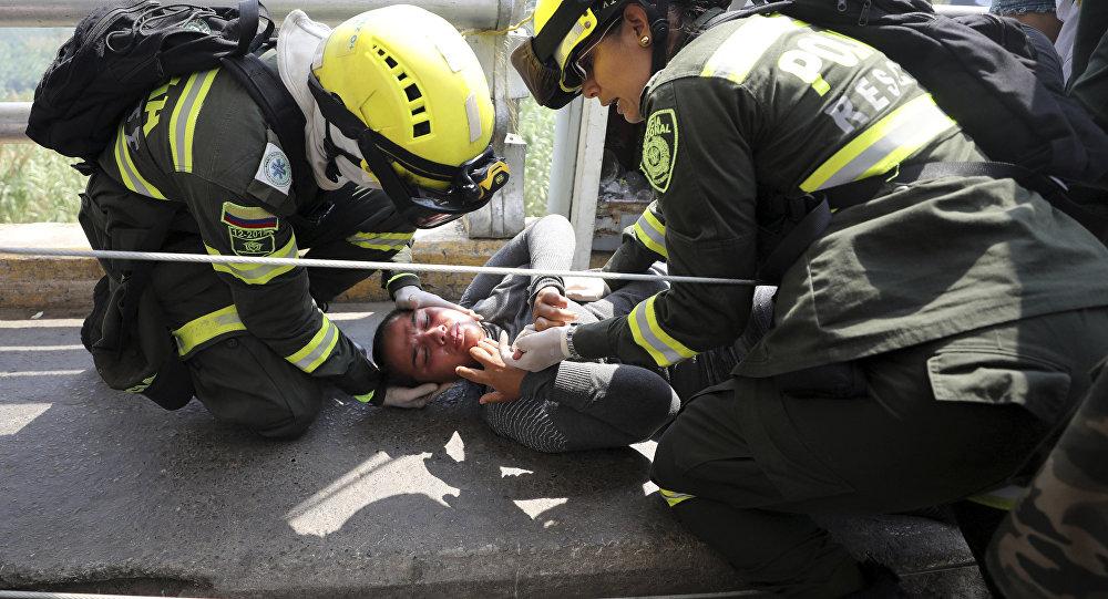 Paramédicos colombianos resgatam venezuelana ferida na Ponte Símon Bolívar, na fronteira entre Colômbia e Venezuela.