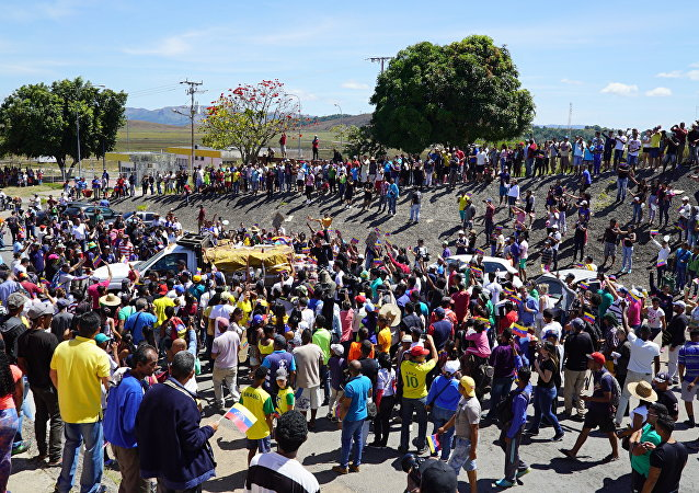 Brasileiros e venezuelanos se reúnem em torno de caminhão da Venezuela com mantimentos enviados pelo Brasil na zona de fronteira