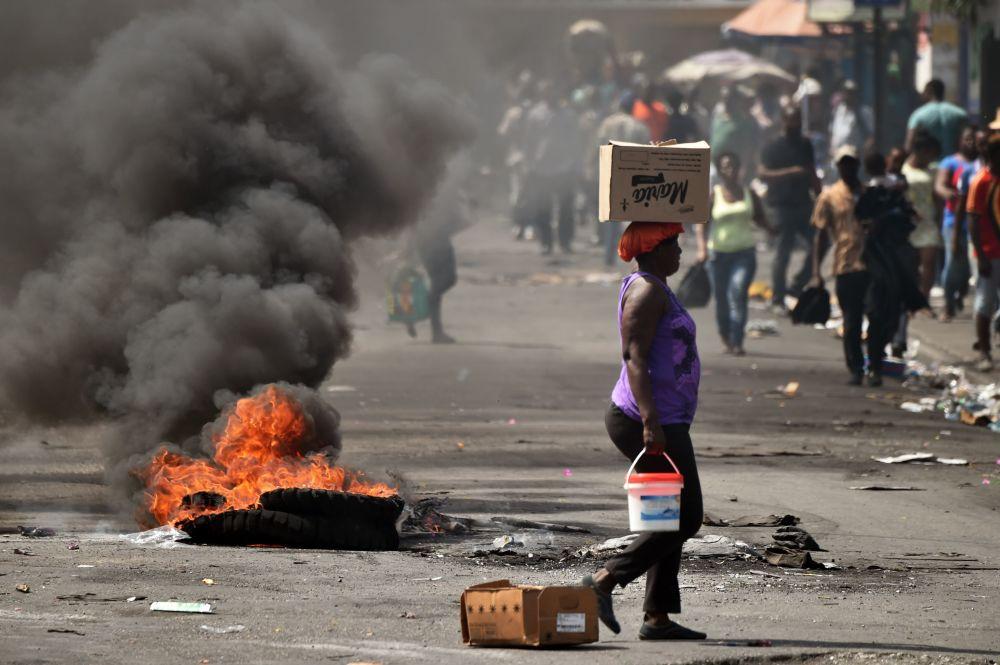 Uma mulher passa diante de pneu ardendo em uma rua de Porto Príncipe, capital do Haiti
