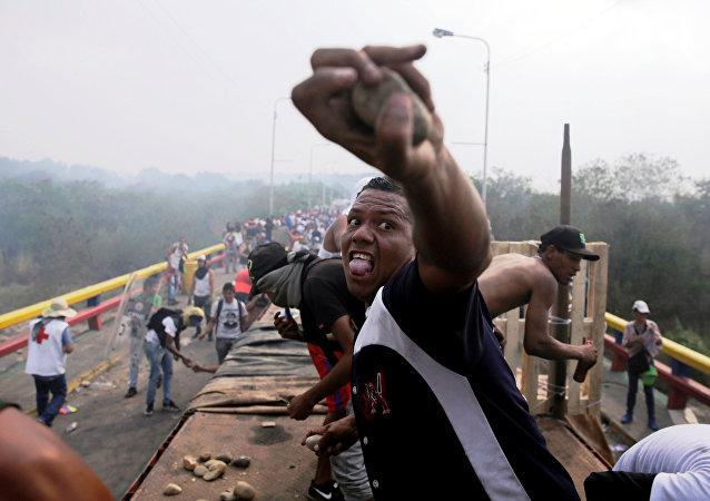 Partidários da oposição confrontam as forças de segurança da Venezuela na ponte Francisco de Paula Santander, na fronteira entre Colômbia e Venezuela, na Colômbia, em 23 de fevereiro de 2019