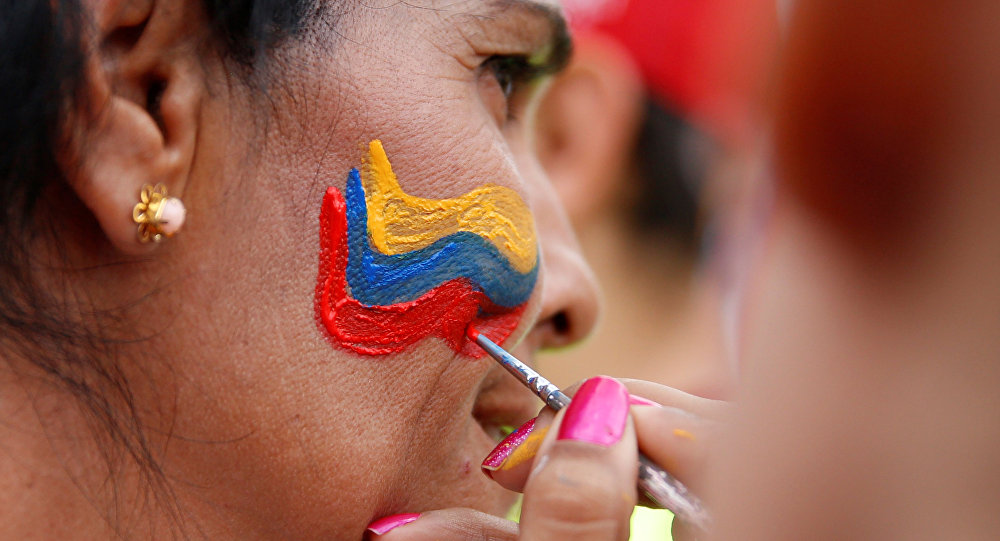 Manifestantes pintam bandeira venezuelana no rosto de uma mulher durante manifestação contra o governo do presidente venezuelano Nicolás Maduro, em Caracas, 26 de outubro de 2016
