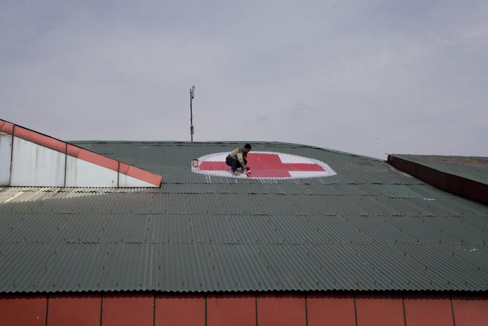 Funcionário desenha o emblema da Cruz Vermelha no telhado do hospital SMHS na Caxemira em meio à escalada nas relações indo-paquistanesas