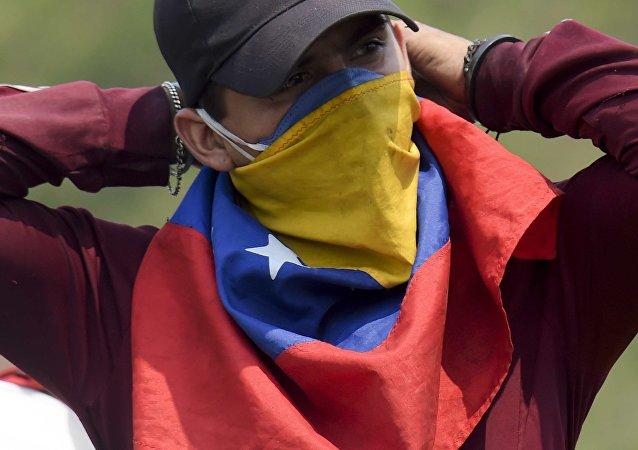 Manifestante com bandeira da Venezuela no rosto
