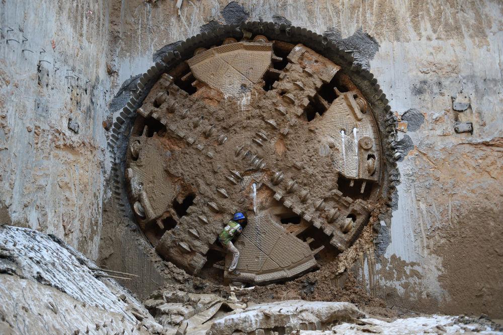 Trabalhador perto de máquina de perfuração para túnel de metrô em Ahmedabad, Índia, 25 de fevereiro de 2019
