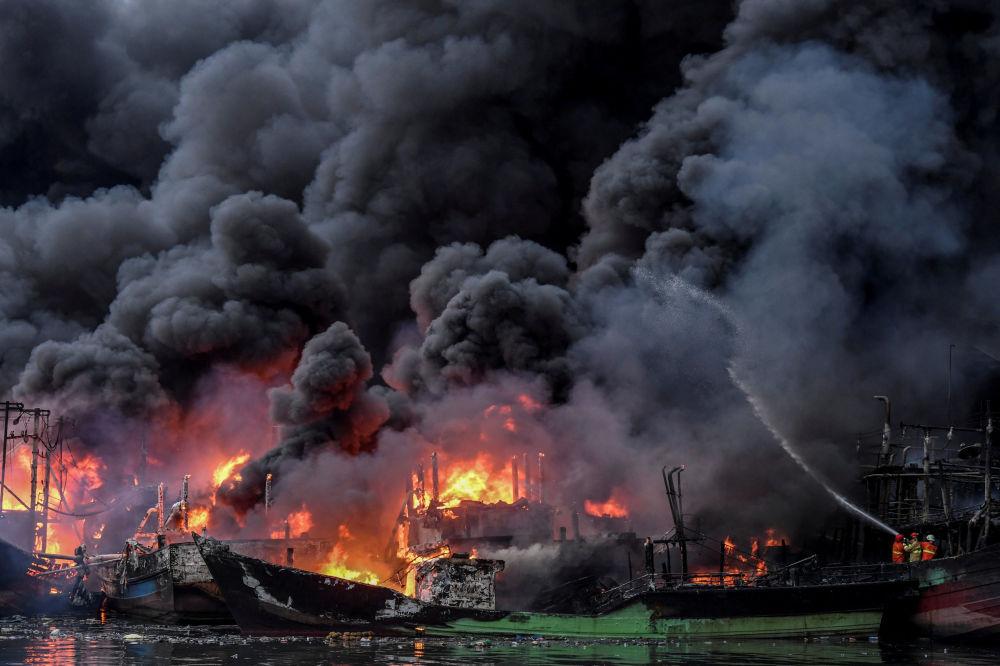 Bombeiros tentam apagar fogo, que está queimando barcos de pesca no porto de Muara Baru, em Jacarta, Indonésia, 23 de fevereiro de 2019