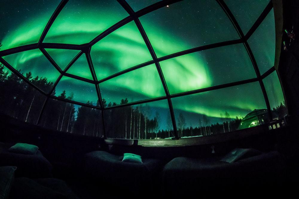 Hóspedes do Arctic Snowhotel admiram o fenômeno a partir de seu quarto com teto de vidro