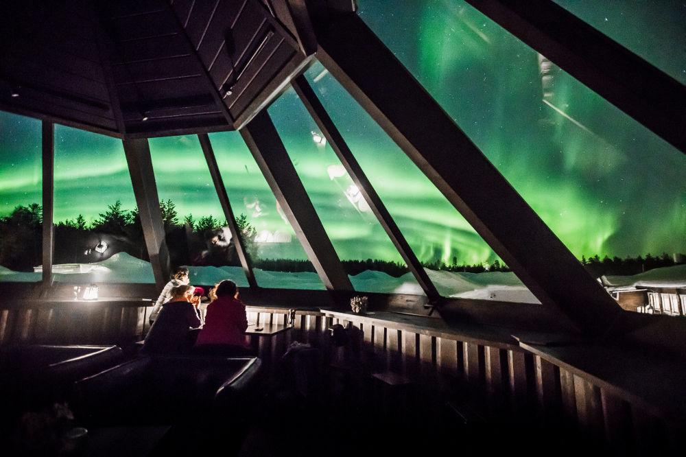 No hotel Arctic Snowhotel em Rovaniemi as pessoas observam a aurora boreal, um fenômeno que aparece no céu em resultado de interação das partículas de vento solar com a as camadas altas da atmosfera da Terra