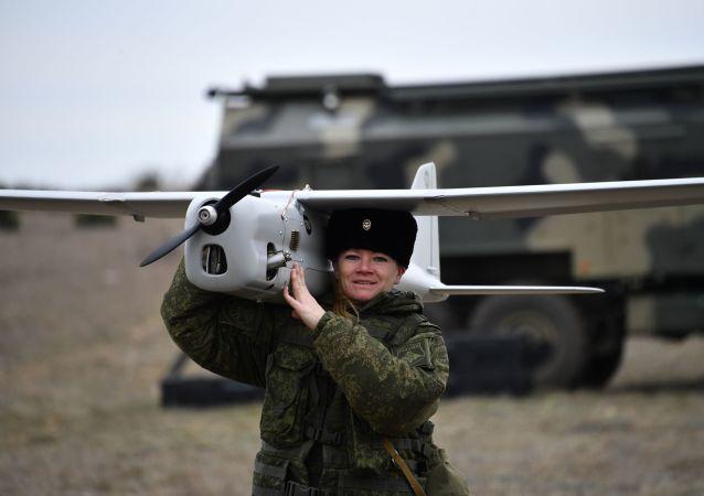 Uma engenheira técnica da unidade feminina de pilotagem de veículos aéreos não tripulados da Brigada de Reconhecimento da Frota do Mar Negro se prepara para o lançamento do drone de reconhecimento Orlan-10