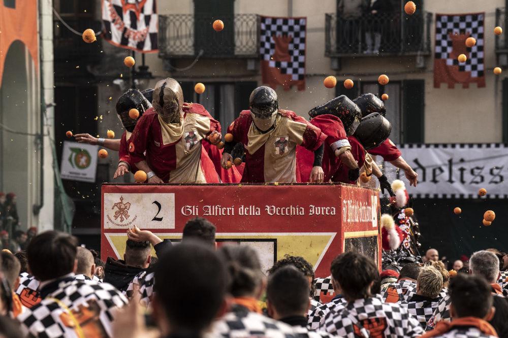 Participantes do tradicional festival Batalha das Laranjas, realizado durante o carnaval em Ivrea, Itália, em 3 de março de 2019