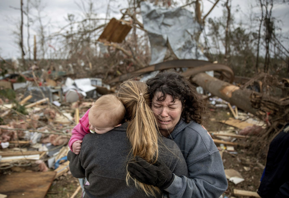 Família chorando nas ruínas de uma casa destruída pelo tornado, no estado norte-americano do Alabama