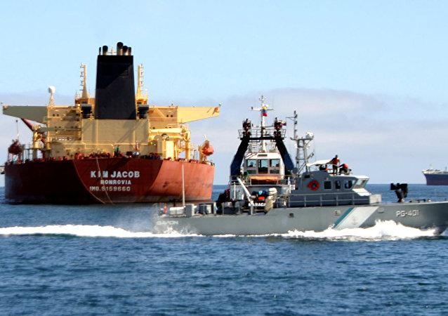 Um barco-patrulha venezuelano passa pelo petroleiro Kim Jacob carregando 1 milhão de barris de petróleo bruto no estado oriental de Anzoátegui, na Venezuela.