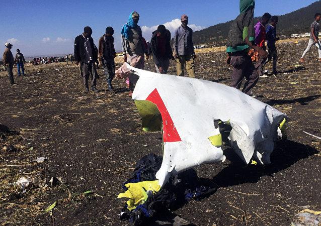 Pessoas passam por parte dos destroços no local do acidente de avião do voo ET302 da Ethiopian Airlines, perto da cidade de Bishoftu, a sudeste de Adis Abeba, Etiópia, 10 de Março de 2019