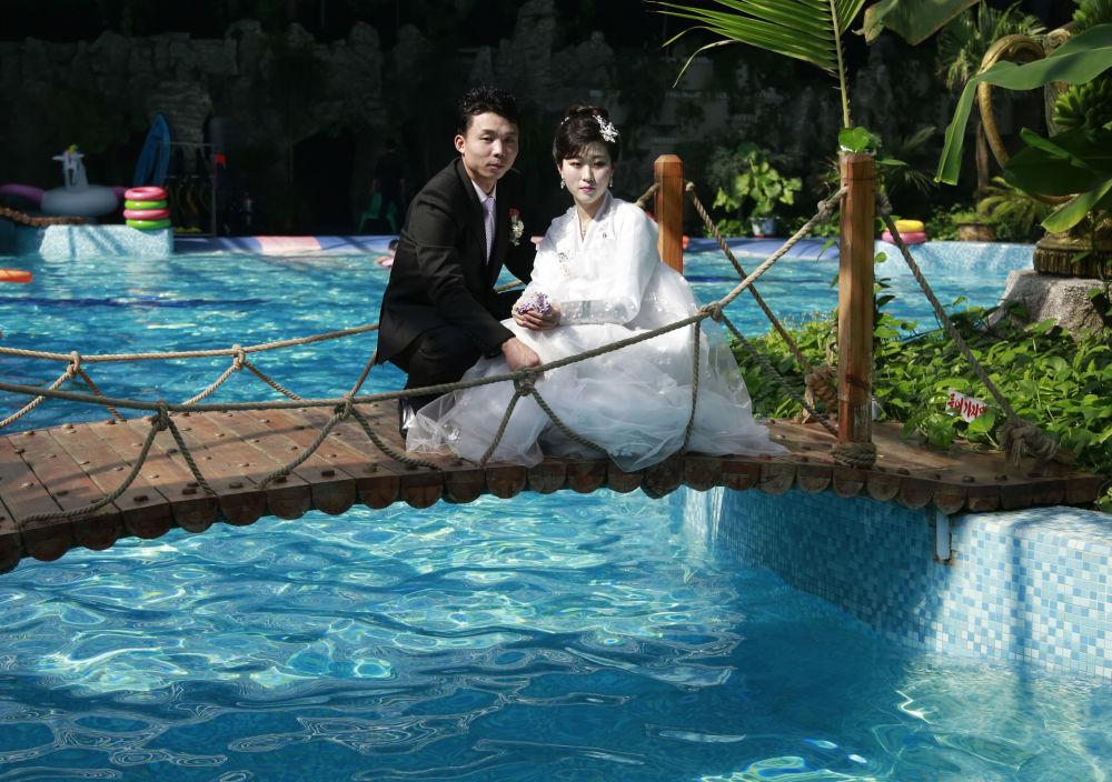 Recém-casados posam para foto em uma piscina coberta em Pyongyang