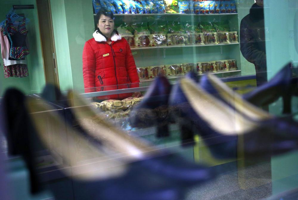Atendente na loja da residência da fábrica têxtil em Pyongyang