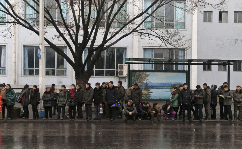 Pessoas esperam trólebus em uma parada em Pyongyang