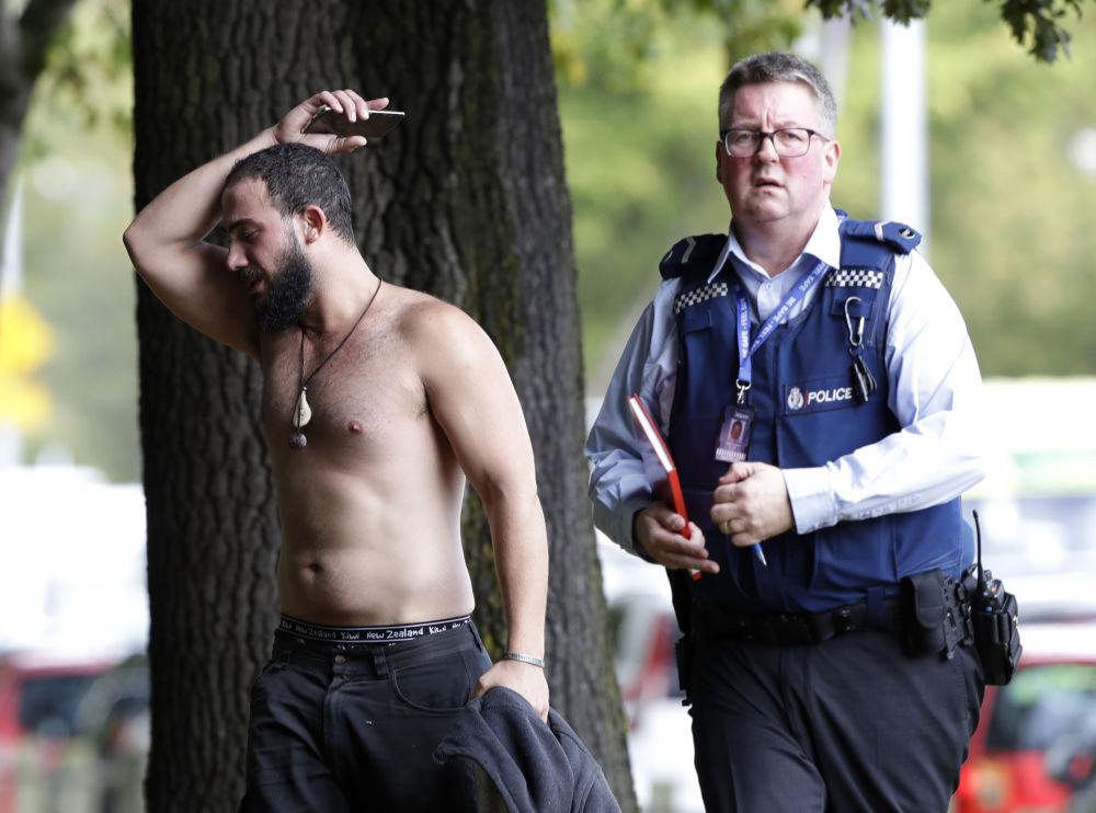 Um homem e um policial perto da mesquita Al Noor após o tiroteio na cidade de Christchurch