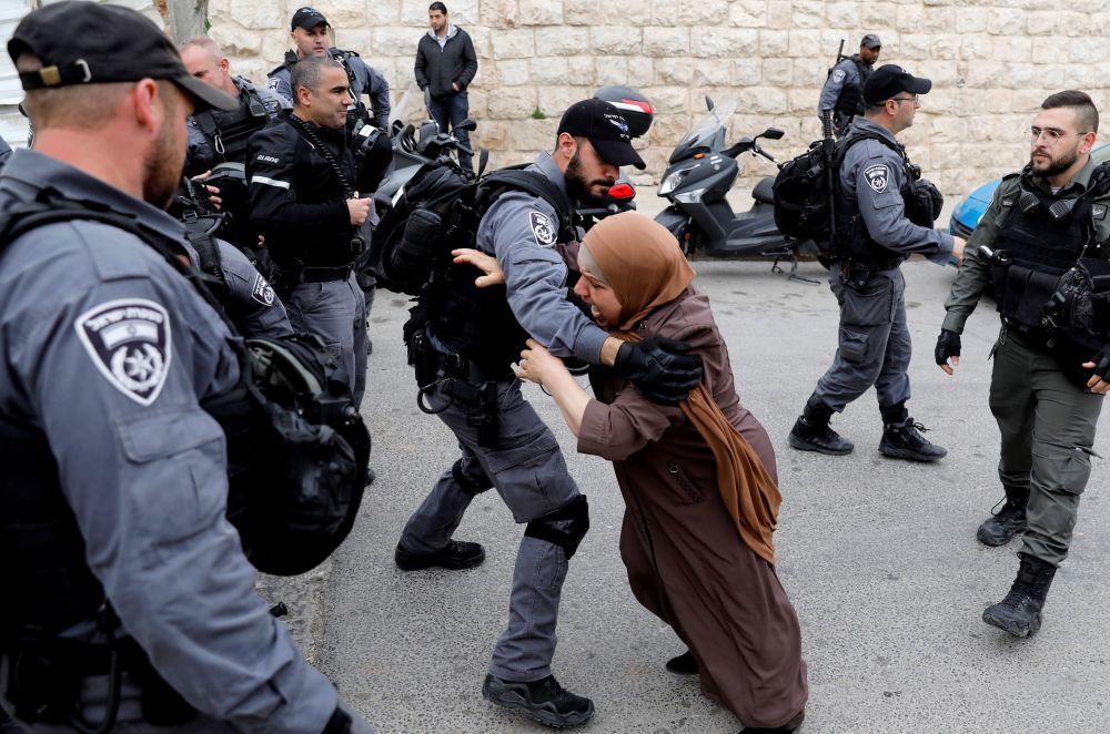 Palestina tenta abrir passagem através dos policiais israelenses após as autoridades israelenses fecharem a entrada no monte do Templo, em Jerusalém