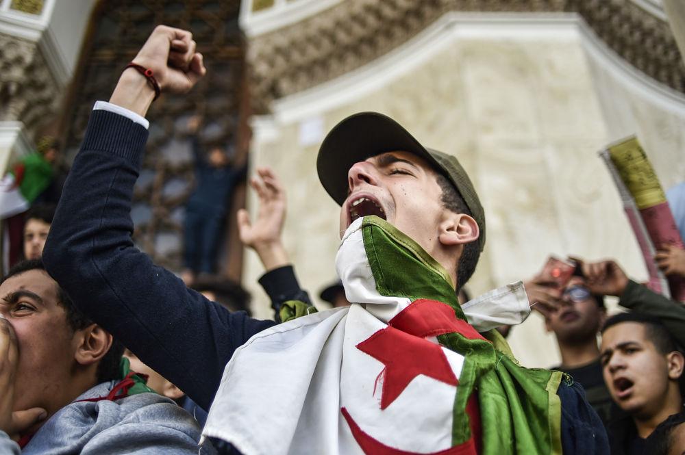 Estudantes argelinos com bandeira nacional durante manifestação contra a candidatura do presidente Abdelaziz Bouteflika às próximas eleições perto da estação principal dos correios na capital argelina