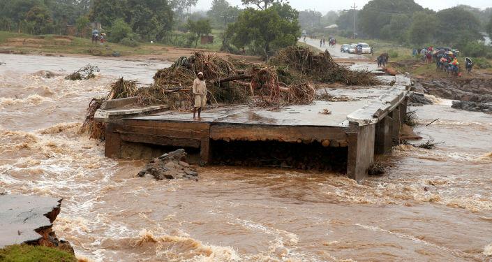 Homem observa água da beira de uma ponte sobre o rio Umvumvu destruída pela passagem do ciclone tropical Idai em Zimbabué, 18 de março de 2019
