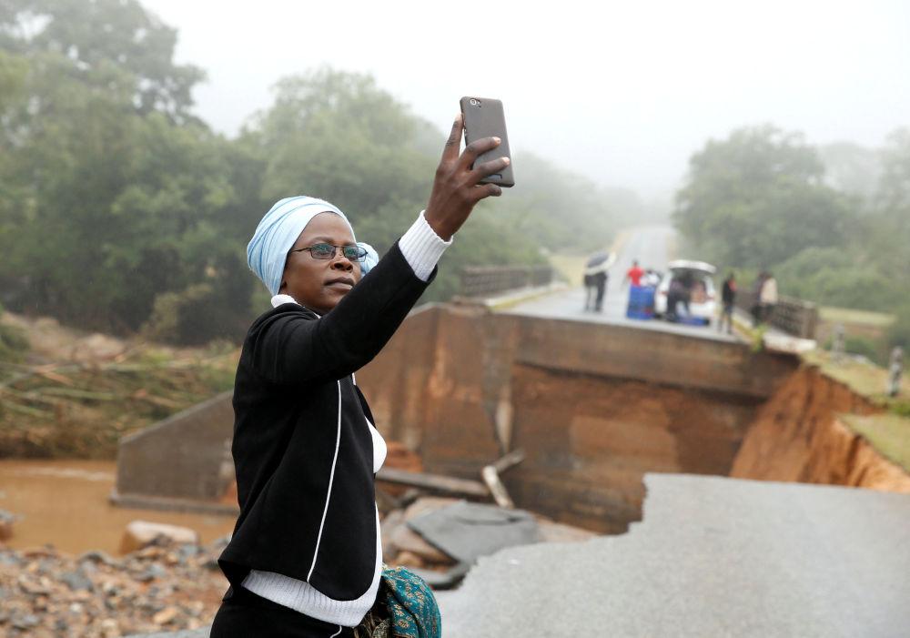 Mulher tira selfie em uma ponte sobre o rio Umvumvu destruída pela passagem do ciclone tropical Idai em Zimbabué