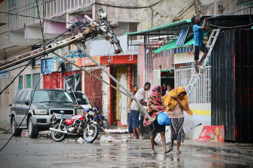 Moradores locais estão tentando se proteger da chuva após a passagem do ciclone tropical Idai, cidade de Beira, Moçambique