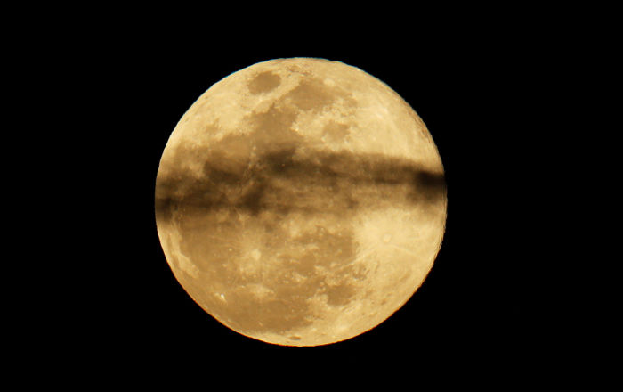 A Superlua se levanta entre as nuvens no céu noturno da Califórnia