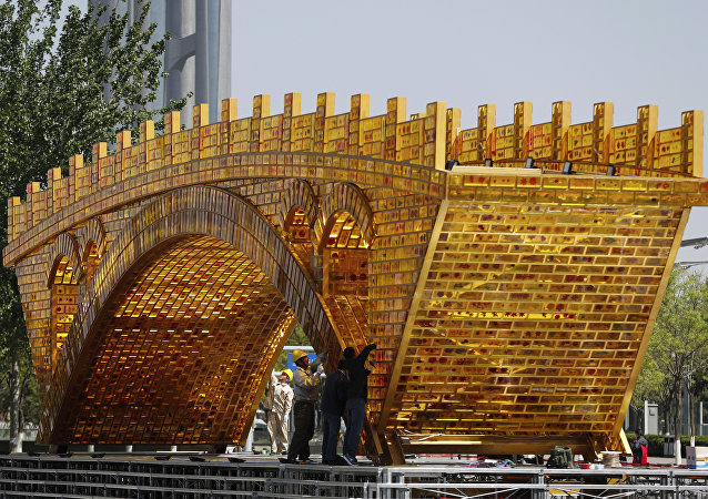 Workers install wires on a 'Golden Bridge of Silk Road' structure on a platform outside the National Convention Center, the venue which will hold the Belt and Road Forum for International Cooperation, in Beijing