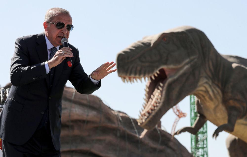 Presidente turco, Recep Tayyip Erdogan, perto de modelo de dinossauro durante a cerimônia de abertura de um parque de diversão em Ancara