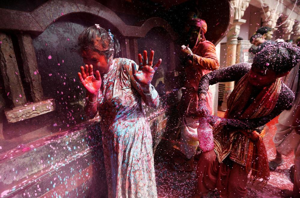Indiano pulveriza água colorida durante o festival religioso Holi, na cidade indiana de Nandgaon