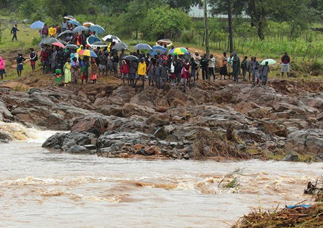Moçambicanos à beira de um rio após o ciclone Idai