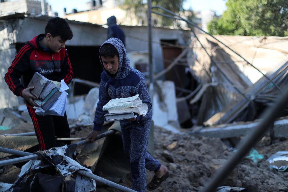 Garotos recolhendo cópias do Corão de uma mesquita, danificada durante o bombardeio de Israel contra Gaza