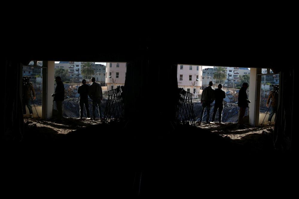 Palestinos ao lado do escritório do chefe do Hamas, Ismail Haniyeh, destruído após o ataque aéreo de Israel contra Gaza