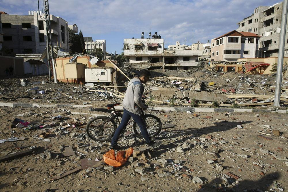Palestino caminhando ao lado do gabinete do líder do Hamas, destruído parcialmente por um ataque aéreo israelense