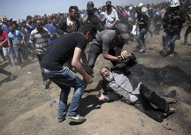 Um palestino idoso cai no chão depois de ser baleado por tropas israelenses durante um protesto na fronteira da Faixa de Gaza com Israel.