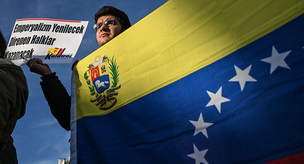 Um ativista de esquerda turco segura uma bandeira nacional venezuelana e um cartaz que se traduz como O imperialismo perderá, o povo resistente vencerá