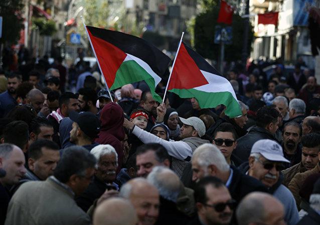 Palestinos seguram bandeiras nacionais em marcha pelas ruas da cidade ocupada de Ramallah pedindo pela unificação da cidade à Faixa de Gaza, 12 de janeiro de 2019