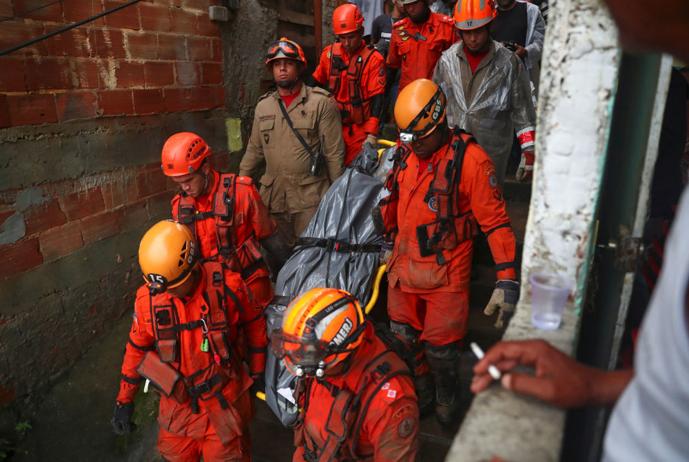Equipes de resgate transportam corpo encontrado em uma área de deslizamento de terra em decorrência de fortes chuvas no Rio de Janeiro